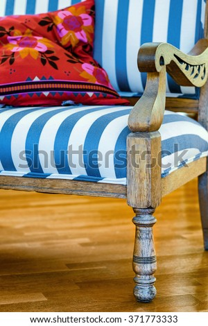 Blue and white striped upholstered chair with pillow - stock photo