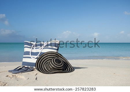 blue and white stripey beach bag flip-flops and hat on the beach - stock photo