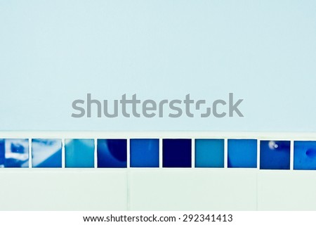 Blue and white tiles against a blue wall - stock photo