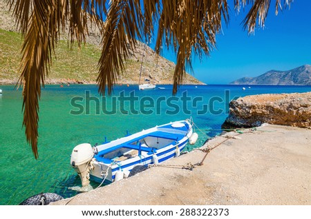 Blue and white wooden boat in cozy Greek port in summer time - stock photo
