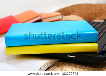 Blue and Yellow Books on the Laptop Closeup - stock photo