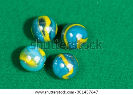 Blue and Yellow Colorful Marble Balls on Green background - stock photo