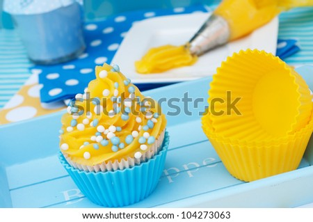Blue and yellow cupcake setting with whipped cream - stock photo