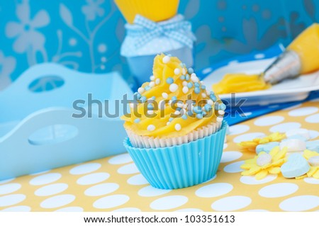 Blue and yellow cupcake with tools in the background - stock photo