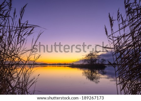Blue and yellow Sunset over a Tranquil lake - stock photo