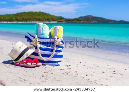 Blue bag, straw hat, flip flops and towel on white beach - stock photo