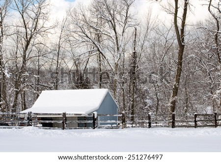 Blue barn in a rural winter setting with snow frosted trees - stock photo