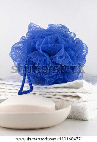 Blue bath puff with clean white towel and soap in dish on white background. - stock photo