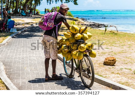 BLUE BAY, MAURITIUS - DECEMBER 27, 2015: Mauritius young man selling coconuts from his bike on the beach Blue Bay, Mauritius. - stock photo