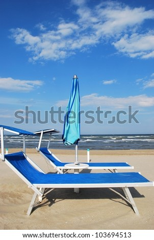 Blue beach chairs and umbrella, Rimini, Italy - stock photo