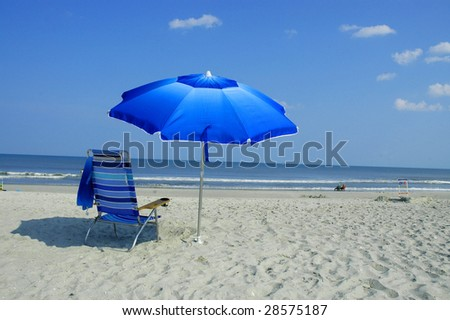 Blue Beach Umbrella and Beach Chair - stock photo