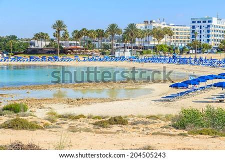Blue beach umbrellas and sunbeds on Sandy Beach in Ayia Napa, Cyprus - stock photo