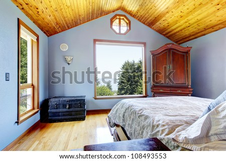Blue bedroom with wood ceiling and bed, large windows interior - stock photo