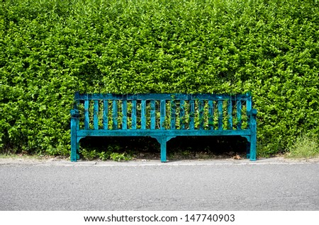 Blue bench on the sidewalk in front of a green fence - stock photo