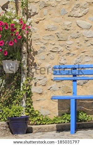 Blue bench with flower wall. Provence. France. - stock photo
