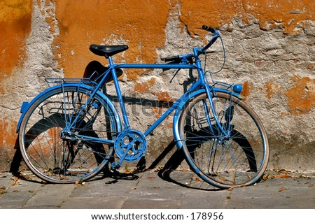 Blue bicycle against an orange wall - stock photo
