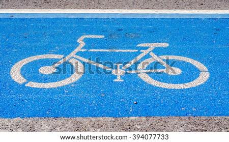Blue bicycle lane signage on street - stock photo