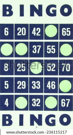 Blue bingo card being used (white chips) - stock photo