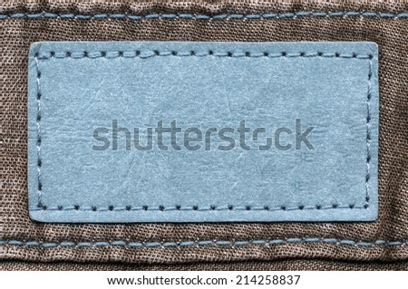 blue blank  label on brown jeans background - stock photo