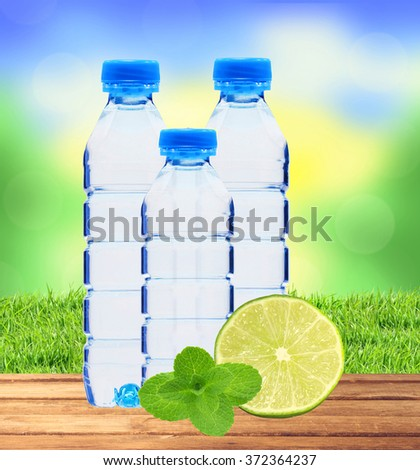Blue bottles with water, mint herb and fresh green lime over nature background - stock photo