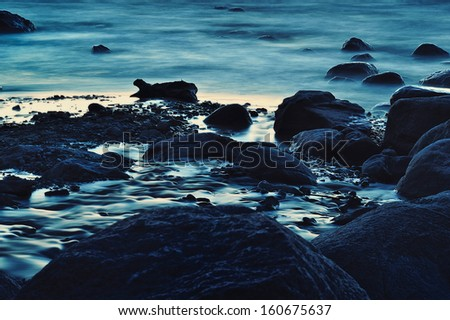 Blue boulders on the seashore in Arambol, Goa  - stock photo
