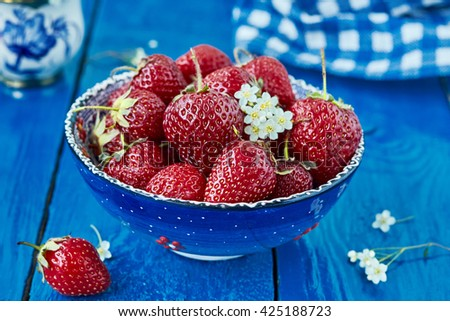 Blue bowl filled with  juicy fresh ripe red strawberries. horizontal - stock photo