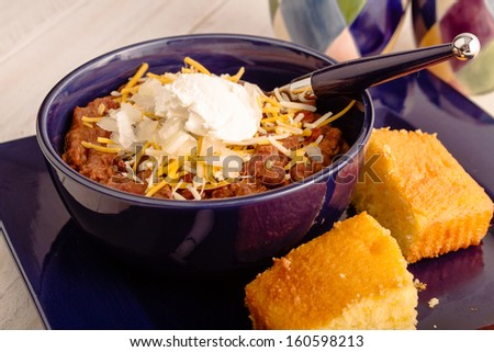Blue bowl of elk meat chili sitting on plate with cornbread - stock photo
