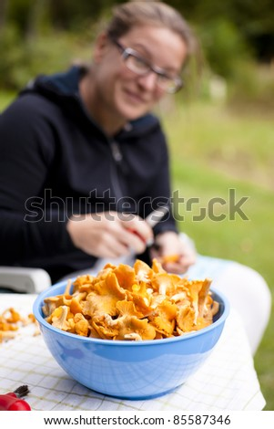Blue bowl with fresh, picked chanterelles. Woman is rinsing the fungus in background - stock photo