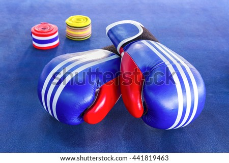 Blue boxing gloves with two rolls of hand bandage on blue exercise mat. - stock photo