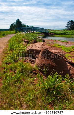 Blue bridge on red sand walking trail in PEI, Canada - stock photo