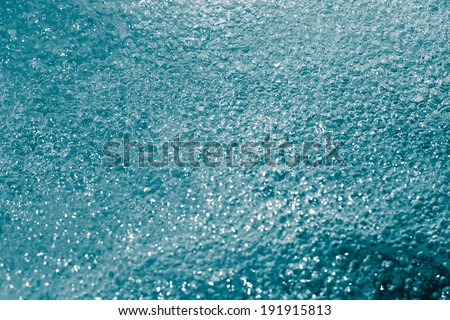 blue bubbling water from beneath the waves - stock photo
