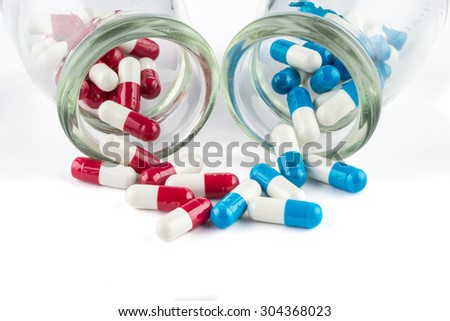 blue capsules and red capsules with Transparent  bottle, healthcare and medicine medication cure - stock photo