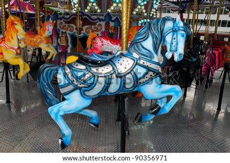 Blue carousel horse on merry-go-round - stock photo