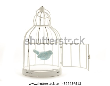 blue ceramic bird hanging in vintage wire painted cage - stock photo