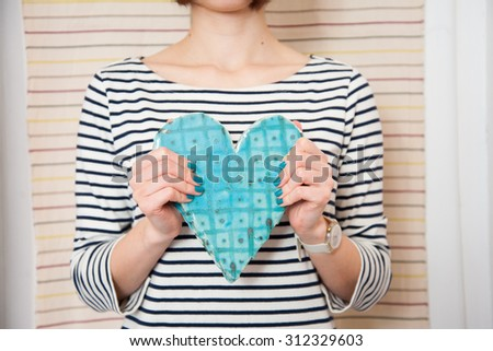 Blue ceramic heart in woman hands - stock photo