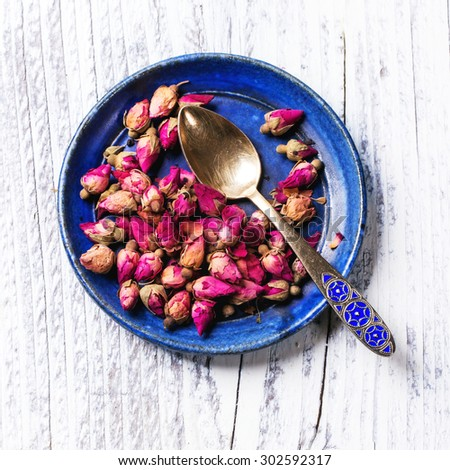 Blue ceramic plate of tea roses and golden tea spoon over white wooden background.. Top view. Square image - stock photo