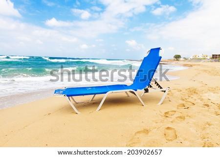 blue chair on Malia beach, Crete, Greece - stock photo