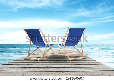 blue chairs and gray pier of wood  - stock photo