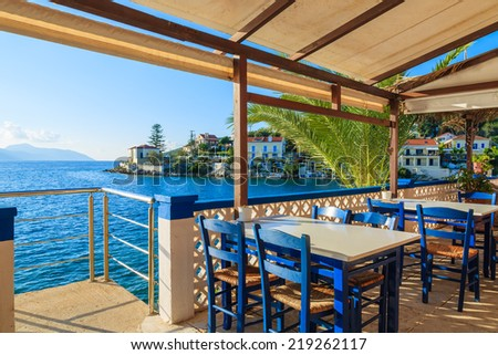 Blue chairs with tables in traditional Greek tavern in Fiskardo port, Kefalonia island, Greece - stock photo