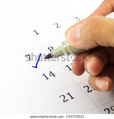 Blue check. Mark on the calendar at 7. - stock photo