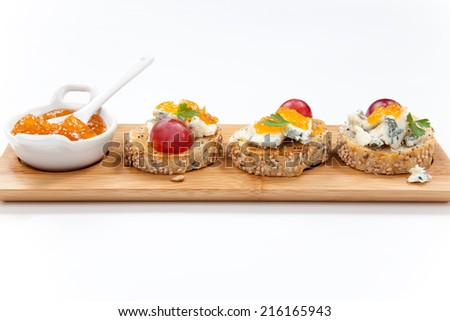 Blue cheese and apricot jam multigrain crostini with grapes and parsley on wooden tray. Apricote jam mini bowl.  - stock photo