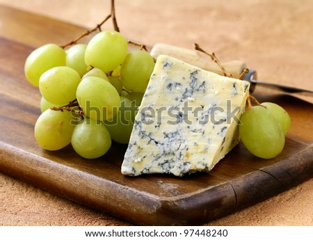 blue cheese and white grapes on a wooden board - stock photo