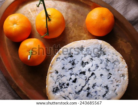 Blue cheese with oranges on metal tray on burlap cloth and wooden table background - stock photo