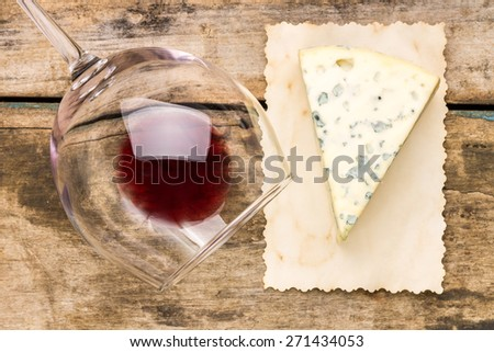 Blue cheese with overturned glass of red wine on vintage paper. Restaurant wine list background. Top view image - stock photo