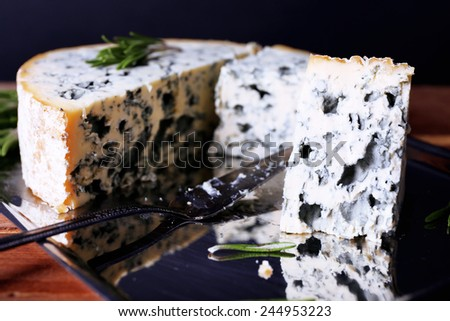 Blue cheese with sprigs of rosemary and blade on metal tray and wooden table background - stock photo