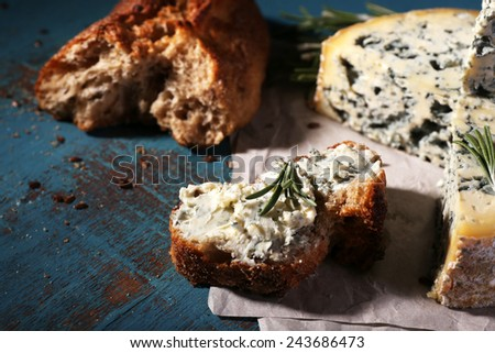 Blue cheese with sprigs of rosemary and bread on sheet of paper and color wooden table background - stock photo