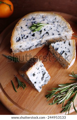 Blue cheese with sprigs of rosemary and orange on wooden board background - stock photo