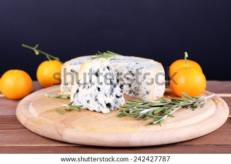 Blue cheese with sprigs of rosemary and oranges on board, wooden table and dark background - stock photo