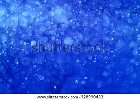 Blue Christmas background. It is made from photo of real snow fall. This blurred snowing can be a Christmas, New Years eve or winter background texture. - stock photo