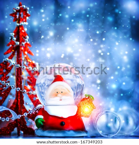 Blue Christmas background with cute snow globe Santa Claus border over blur bokeh lights, magic of Christmas eve and winter holidays, Xmas greeting card - stock photo